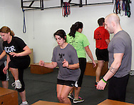 (from left) Tracy Belt of Kettering, Anne Keeton of Kettering, Abby Griest of West Carrollton, Aaron Pertner of Dayton and owner Jason Hoskins of Dayton during a workout of the day session at Vigor Crossfit in Moraine, Wednesday, January 25, 2012.