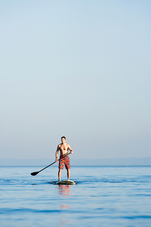 A late 30's Caucasian man on a stand up paddle board on the Puget Sound near Seattle, WA.
