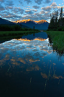 On a beautiful early summer morning in the Canadian Rockies, the first light of day dresses the mountains surrounding Vermillion lakes, while puffy clouds reflect in its still waters. Vermillion lakes has been photographed countless times, but there are always new photographic opportunities, waiting to be discovered.
