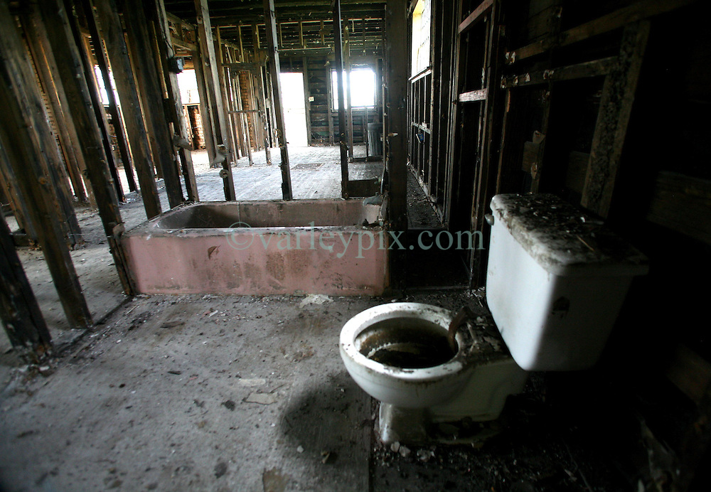 29 August 2006. New Orleans, Louisiana. Lower 9th ward. On the one year anniversary of hurricane Katrina, and most of the area remains derelict and abandoned. A toilet and bath are the only contents that remain in one devastated house.<br /> Photo Credit©; Charlie Varley/varleypix.com