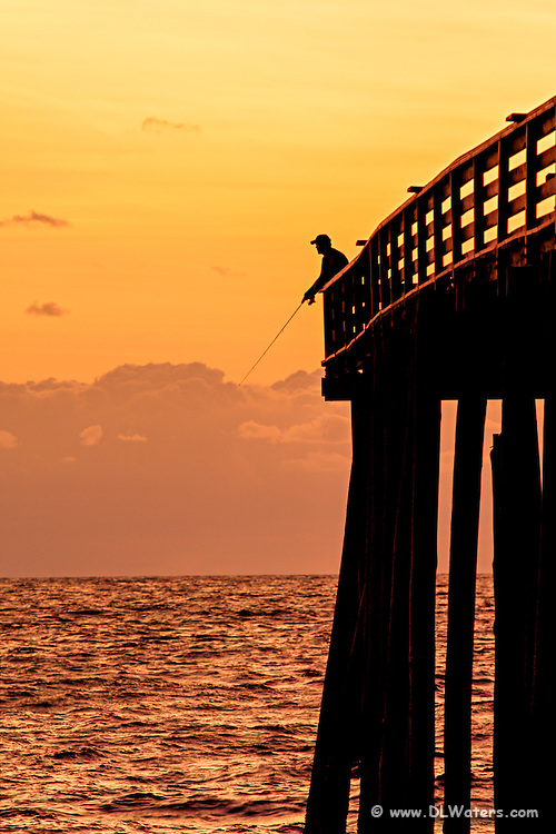 Picture of a fishermen silhouetted at the end of Kitty Hawk Pier.