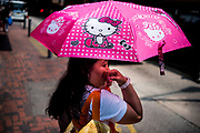 Hong Kong, China - A young girl carries a Hello Kitty umbrella on May 03, 2018. Hello Kitty, which started in 1974 as a moonfaced cartoon cat on a coin purse, has emerged into a global icon of cuteness with about 50,000 different products on sale in 60 nations.
