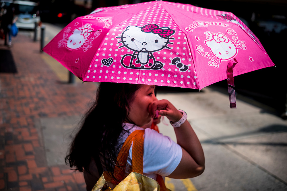 Hong Kong, China - A young girl carries a Hello Kitty umbrella on May 03, 2018. Hello Kitty, which started in 1974 as a moonfaced cartoon cat on a coin purse, has emerged into a global icon of cuteness with about 50,000 different products on sale in 60 nations.Hong Kong, Chine - Une jeune fille porte un parapluie Hello Kitty le 3 mai 2018. Hello Kitty, qui a vu le jour en 1974 sous la forme d'un chat de dessin animé au visage lune sur un porte-monnaie, est devenu une icône mondiale de beauté avec environ 50.000 produits différents en vente dans 60 pays.