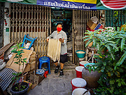 "29 DECEMBER 2018 - BANGKOK, THAILAND: A woman carries longevity noodles out of the shophouse to drying racks in front of her home. The family has been making traditional ""mee sua"" noodles, also called ""longevity noodles"" for three generations in their home in central Bangkok. They use a recipe brought to Thailand from China. Longevity noodles are thought to contribute to a long and healthy life and  are served on special occasions, especially Chinese New Year, which is February 4, 2019. These noodles were being made for Chinese New Year.        PHOTO BY JACK KURTZ"