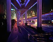 Un couple marche main dans la main la nuit sous une autoroute suspendue de Shanghai en Chine..Le de?veloppement effre?ne? de cette me?gapole a entraine? la multiplication des autoroutes urbaines..La lumie?re bleute?e qui les e?claire leur donne aspect irre?el..