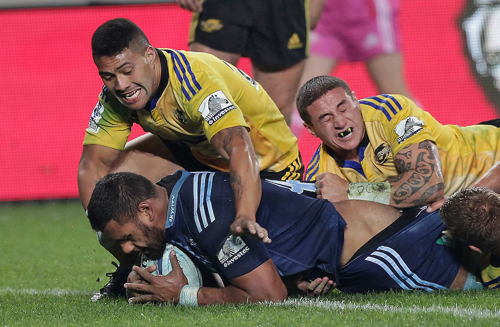 Blues' Patrick Tuipulotu scores arty beating Hurricanes' Ardie Savea and TJ Perenara in a Super Rugby match, Eden Park, Auckland, New Zealand, Saturday, May 31, 2014.  Credit:SNPA / David Rowland