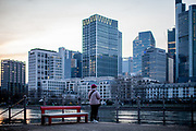 """Germany banned gatherings of more than 2 people called """"social distancing"""" because of the coronavirus. A woman at the shore of river Main in Frankfurt which is very empty on a - normally very busy - Thursday evening."""