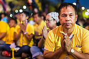 05 MAY 2104 - BANGKOK, THAILAND:  A supporter of the Thai monarchy prays for the King at an anti-government pro-monarchy rally in Bangkok. Thousands of Thais packed the area around Sanam Luang and the Grand Palace Monday evening for a special ceremony to mark Coronation Day, which honored the 64th anniversary of the coronation of Bhumibol Adulyadej, the King of Thailand. Many of the people also support the anti-government movement led by Suthep Thaugsuban. Most of the anti-government protesters are conservative supporters of the monarchy.   PHOTO BY JACK KURTZ