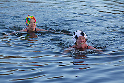 © Licensed to London News Pictures. 25/12/2013. London, UK. Members of the Serpentine Swimming Club go for a quick dip after the completion of the Serpentine Swimming Club's annual Christmas morning 'Peter Pan Cup' race in Hyde Park, London, today (25/12/2013). The race, which takes place every Christmas Day on the Serpentine River, takes its name from from the novel by J.M.Barrie after the author presented the first Peter Pan Cup in 1904. Photo credit: Matt Cetti-Roberts/LNP