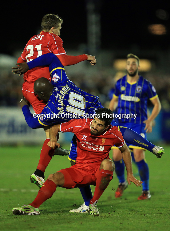 5 January 2015 - The FA Cup 3rd Round - AFC Wimbledon v Liverpool - Adebayo Akinfenwa of AFC Wimbledon collides with Lucas Leiva and Emre Can of Liverpool  - Photo: Marc Atkins / Offside.