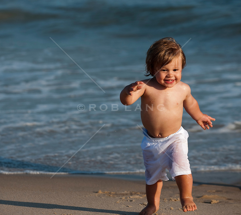 2 year old boy running on the beach in East Hampton