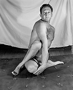 Teacher and advisor to school newspaper on gym matte in hatha yoga pose