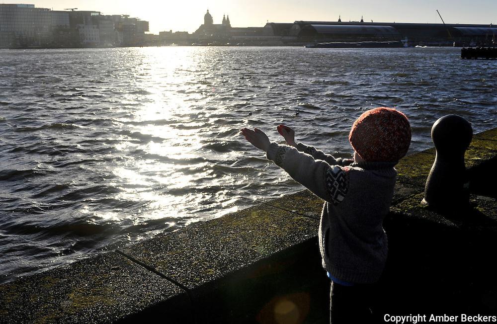 Nederland, Amsterdam, 30 januari 2013.Een jongetje staat aan de noord kant van het IJ en schat met zijn armen en handen hoe lang een boot is. (Kind van de fotograaf).A boy stands on the north side of the IJ-river and tries to figure out how long a boat is.