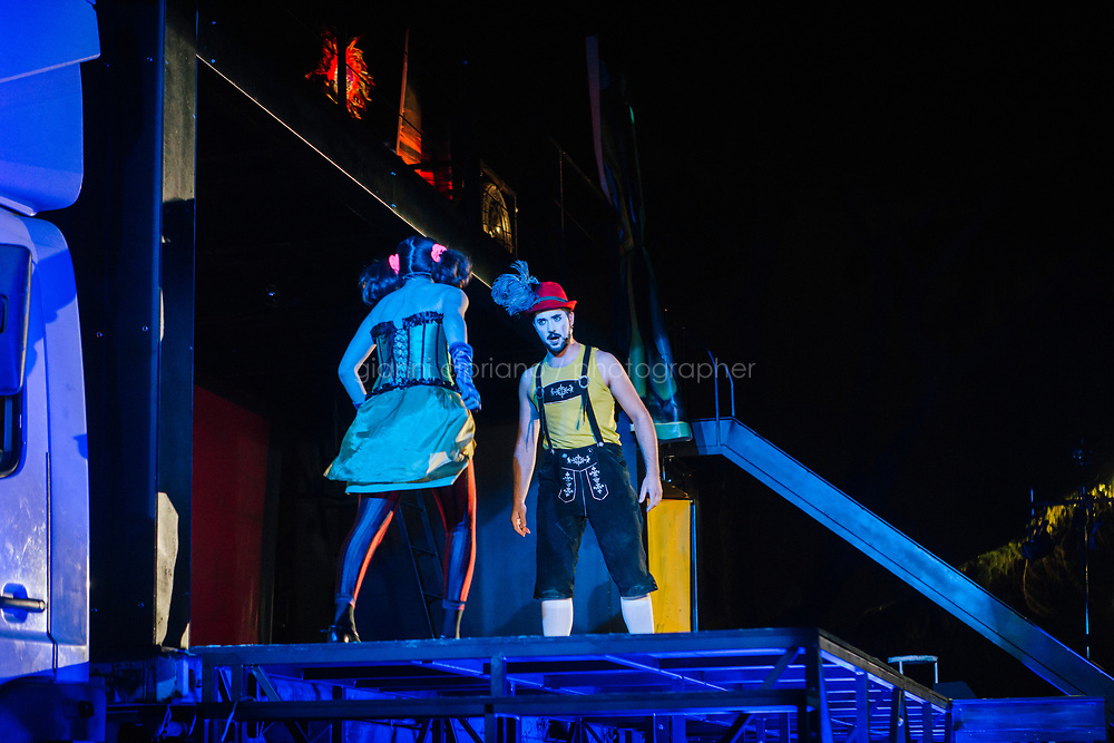 ROME, ITALY - 27 JUNE 2017: (L-R) Opera singer Reut Ventorero (in the role of Zerlina) and Federico Cavarzan (in the role of Masetto) are seen here on stage performing in the &quot;Don Giovanni OperaCamion&quot;, an open-air opera performed on a truck in San Basilio, a suburb in Rome, Italy, on June 27th 2017.<br /> <br /> Director Fabio Cherstich&rsquo;s idae of an &ldquo;opera truck&rdquo; was conceived as a way of bringing the musical theatre to a new, mixed, non elitist public, and have it perceived as a moment of cultural sharing, intelligent entertainment and no longer as an inaccessible and costly event. The truck becomes a stage that goes from square to square with its orchestra and its company of singers in Rome. <br /> <br /> &ldquo;Don Giovanni Opera Camion&rdquo;, after &ldquo;Don Giovanni&rdquo; by Wolfgang Amadeus Mozart is a new production by the Teatro dell&rsquo;Opera di Roma, conceived and directed by Fabio Cherstich. Set, videos and costumes by Gianluigi Toccafondo. The Youth Orchestra of the Teatro dell&rsquo;Opera di Roma is conducted by Carlo Donadio.