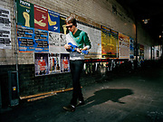 Young man walking down street playing blue ukulele.