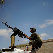 A rebel fighter shoots an anti aerial machine gun in direction of a pro-Gaddafi convoy moving towards Sabratha.