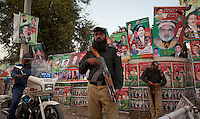 Punjab police stand guard outside an election campaign rally for supporters of Imran Khan, chairman of the Pakistan Tehreek-e-Insaf, in Multan, Pakistan, Monday, May 6, 2013. Pakistan is due to hold a general election on May 11, the first transition of power between democratically elected governments.