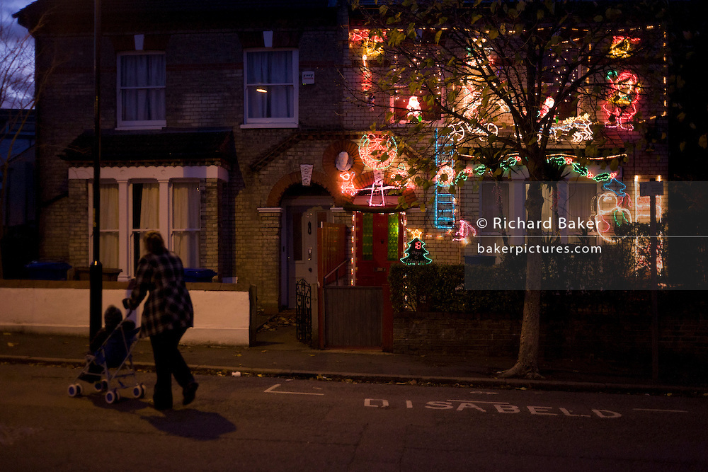 A mother and child walks past a residential house adorned with a mass of wasteful Christmas lights, the only one in this Nunhead, south London street.