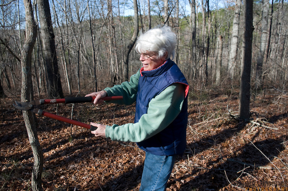 """Date: 1/08/09.Desk: STL.Slug: WOMYN.Assign ID: 30074969A..Emily Greene, 62, trims a branch while on a hike at Alapine, a """"womyn's land"""" or lesbian intentional community, in rural northeast Alabama. ...(*the exact town/location of the community cannot be revealed in the caption or article, per agreement with the subjects)..Photo by Angela Jimenez for The New York Times .photographer contact 917-586-0916"""