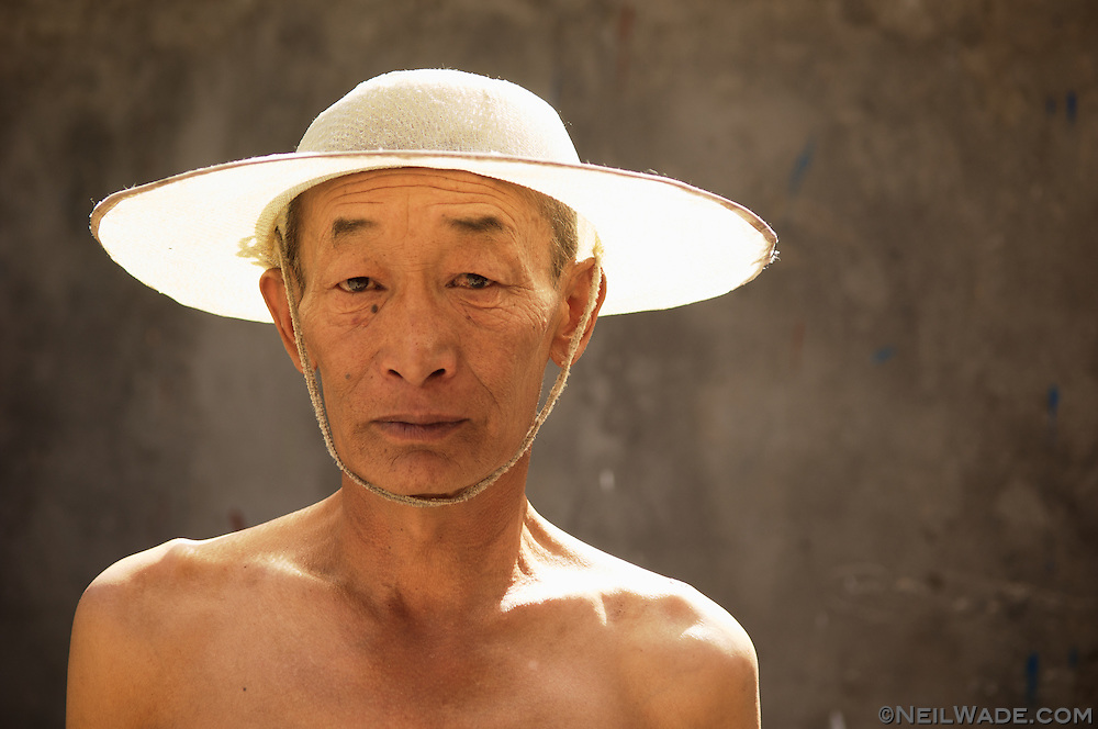 A portrait of a shirtless Tibetan man with a straw hat in Dege, China.