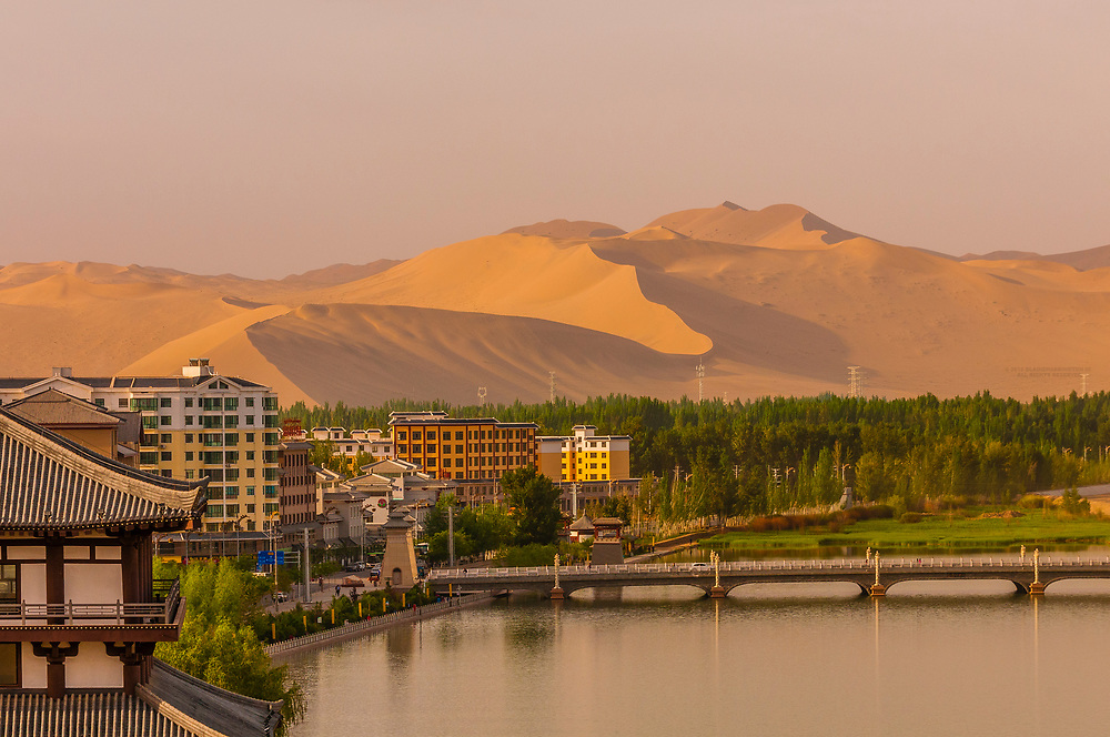 The Danghe River with the massive Singing Sand Mountain (Mingsha Shan) behind, Dunhuang, Gansu Province, northwest China. Dunhuang is along the route of the Silk Road and is on the edge of the Gobi Desert.
