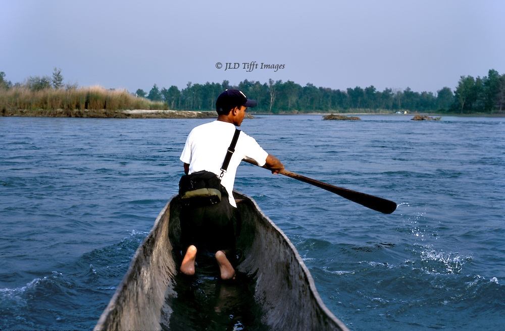 Bardia National Park guide paddles a dugout canoe across the Karnali river.
