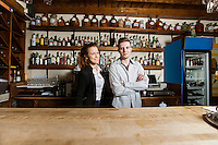 Portrait of confident bartenders at counter in restaurant