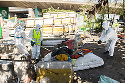 © Licensed to London News Pictures . 09/05/2017. Paris, France . Environmental health workers clean up the scene where French police have cleared approximately 1000 people from an ad hoc roadside camp under roadways along a central reservation , in which migrants were living , in Porte de la Chapelle in North Paris , this morning (9th May 2017) . Photo credit: Joel Goodman/LNP