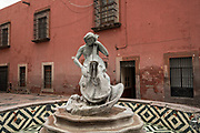 Water fountain musician playing the cello behind the San Francisco Church in the old colonial section of Santiago de Queretaro, Queretaro State, Mexico.
