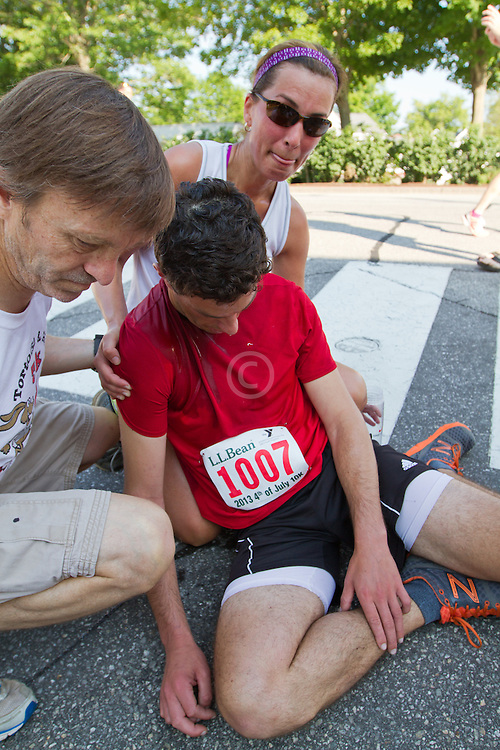 LL Bean 10K road race: fallen runner assisted on side of course by Brain Berkemeyer, Tammy Heathco