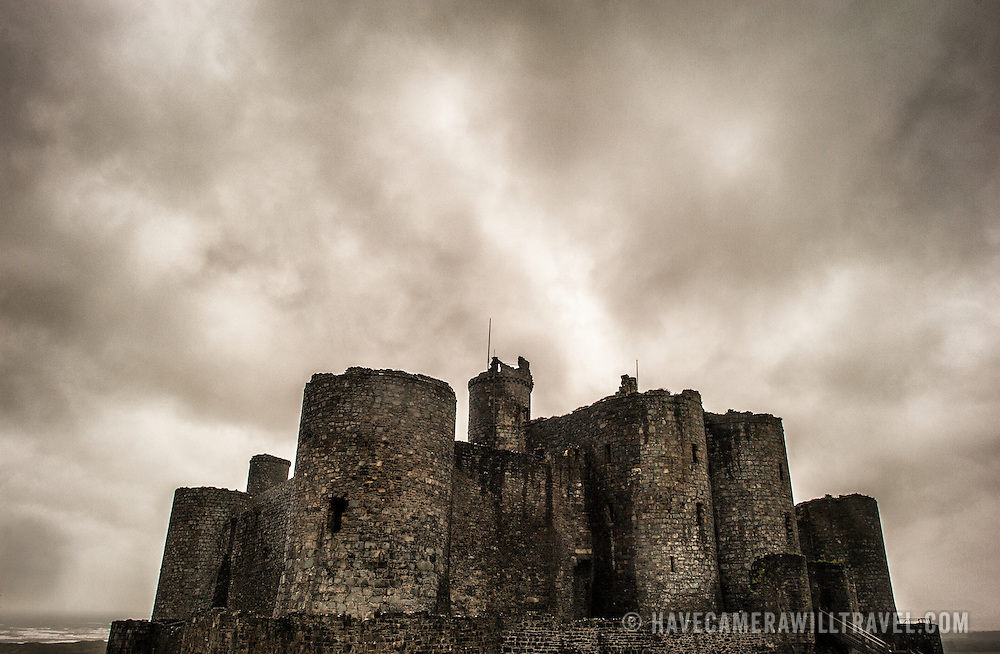 Heavy, ominous clouds hang over Harlech Castle in Harlech, Gwynedd, on the northwest coast of Wales next to the Irish Sea. The castle was built by Edward I in the closing decades of the 13th century as one of several castles designed to consolidate his conquest of Wales.