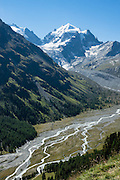 "The icy Bernina Range rises above Ova da Roseg river valley, near Pontresina, Switzerland, in the Bernina Alps, Europe. Tschierva Glacier flows from Piz Roseg (3937 m). Val Roseg is in the Swiss canton of Graubünden (or Grisons / Grigioni / Grischun); the lower Roseg Valley is in Pontresina, whereas the upper valley is in an exclave of Samedan Municipality. Hike from Pontresina up Roseg Valley to Fuorcla Surlej for stunning views of Piz Bernina and Piz Roseg, finishing at Corvatsch Mittelstation Murtel cable car. Walking 14 km, we went up 1100 meters and down 150 m. Optionally shorten the hike to an easy 4 km via round trip lift. The Swiss valley of Engadine translates as the ""garden of the En (or Inn) River"" (Engadin in German, Engiadina in Romansh, Engadina in Italian), and is part of the Danube basin."