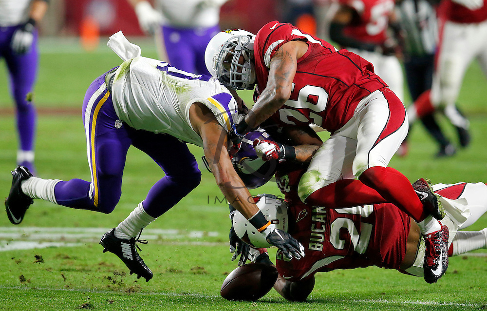 Arizona Cardinals strong safety Deone Bucannon (20) forces Minnesota Vikings wide receiver Jarius Wright (17) to fumble as free safety Rashad Johnson (26) during the first half of an NFL football game, Thursday, Dec. 10, 2015, in Glendale, Ariz. Bucannon recovered the fumble for the Cardinals. (AP Photo/Rick Scuteri)