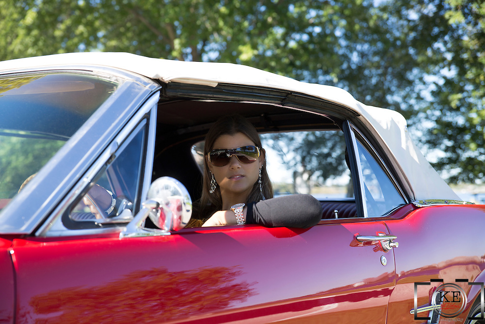 A young lady in sunglasses, behind the wheel of a red 1966 Ford Mustang Convertible
