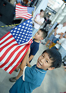 Garden City, New York, U.S. July 20, 2019. Two young boys wave American Flags as the model of the Lunar Module starts to descend from ceiling, at the exact time the Apollo 11 Lunar Module, The Eagle, landed on the Moon 50 years ago, at the Apollo at 50 Countdown Celebration at Cradle of Aviation Museum in Long Island.