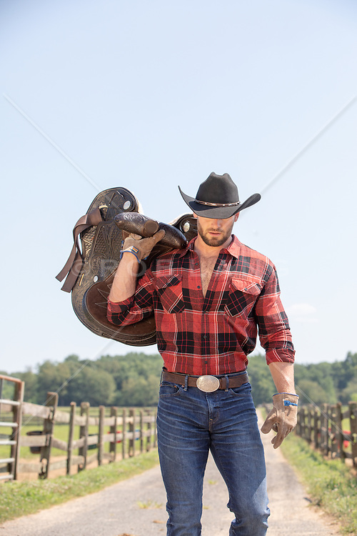rugged cowboy with a saddle on a ranch