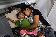 A mother falls asleep with her severely dehydrated child in the medical tent for evacuees in the city's largest stadium in Zamboanga, Mindanao, The Philippines on November 4, 2013. These Internally Displaced People (IDP) had taken refuge in this stadium after surviving the 3 week long attack by MNLF rebels. Photo by Suzanne Lee for SPRINT-IPPF
