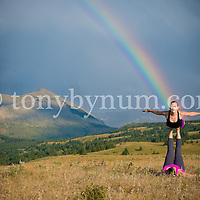 two women doing acrobatic yoga in mountain medow under bright rainbow