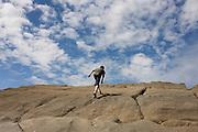 A 13 year-old teenage boy walks up steep sandstone rocks in the coastal cove of Trentishoe in north Devon.