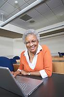 Mature female student using laptop in lecture theatre, portrait