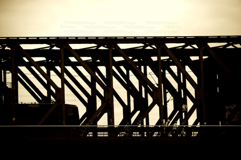 The silhouette and the outline of a railway bridge with a train and cyclists.