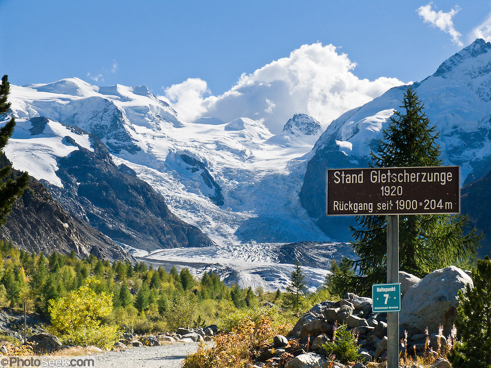 "A sign marks the extent of Morteratsch Glacier in 1920, showing fast retreat. Morteratsch Glacier (Romansh: Vadret da Morteratsch) flows from the Bernina massif in Upper Engadine, Switzerland, the Alps, Europe. From 1878-1998, Morteratsch Glacier retreated 1.8 kilometers (1.1 miles). Melting accelerated to 30 meters (98 feet) per year from 1999–2005. An overwhelming consensus of world scientists agree that global warming is indeed happening and humans are contributing to it through emission of heat-trapping ""greenhouse gases,"" primarily carbon dioxide (see www.ucsusa.org). Since the industrial revolution began, humans have increased atmospheric CO2 concentration by 35% (through burning of fossil fuels, deforesting land, and grazing livestock). A favorite walk is from Morteratsch (second train stop from Pontresina towards Bernina Pass) to Refuge Boval, which has a restaurant and overnight lodging. The trail is well graded, 5 or 6 miles round trip with 2700 feet gain. Return via lower trail for partial loop. The Swiss valley of Engadine translates as the ""garden of the En (or Inn) River"" (Engadin in German, Engiadina in Romansh, Engadina in Italian)."