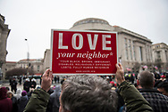 """A man holds up a """"love your neighbor"""" sign as people wait along Pennsylvania Avenue for the start of inaugural parade.<br /> <br /> (Washington D.C. - January 20, 2017)"""