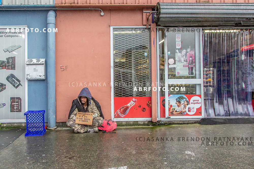 Tu holding a sign reading 'The struggle is real, don't hate, donate' sits in the rain begging outside a bakery in Henderson on the 6th of June 2018. Asanka Brendon Ratnayake for The New York Times.