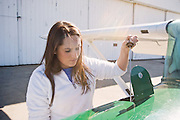 Erin Derosa goes through her pre-flight checks on a Cessna 152 on Monday, October 19, 2009 at The Gordon K. Bush Ohio University Airport. here, she checks tha aircraft's oil.