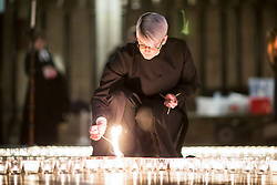 © Licensed to London News Pictures. 24/01/2018. York UK. Verger Jessica Cook lights one of the 600 candle's being lit in the form of the Star of David in York Minster tonight in memory of more than 6 million Jews murdered by the Nazis in World War Two. The cathedral's commemoration is one of a series of events taking place across the City of York during Holocaust Memorial Week. The theme for this year's commemoration is The Power of Words. Photo credit: Andrew McCaren/LNP