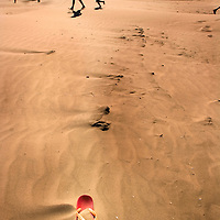 People on a beach with a red flipflop in the sand