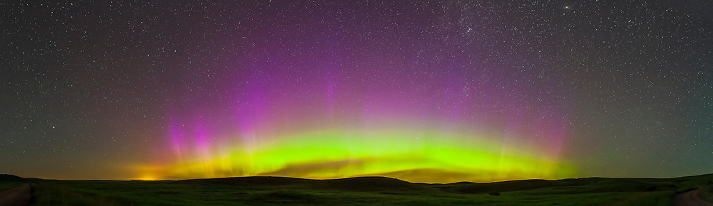 A panorama of the Northern Lights, aurora borealis, taken July 13/14, 2013, from the Reesor Ranch in southwest Saskatchewan, in the Cypress Hills. This is a 6-section panorama, each segment a 30-second exposure with the 24mm lens at f/2.8 and Canon 5D MkII at ISO 1600. Stitched with Photoshop Photomerge command. The glow at left on the horizon is Medicine Hat, Alberta.