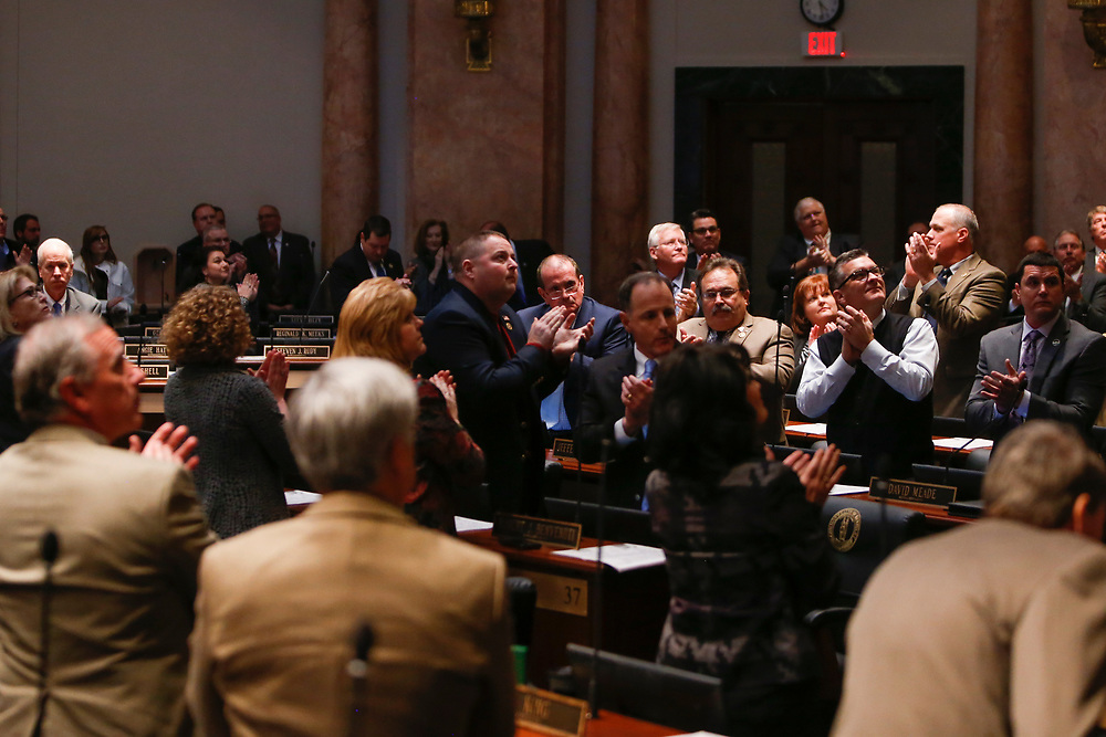 The Kentucky General Assembly applauds Rep. Jeff Hoover's wife, Karyn Hoover, in attendance after he resigned as the Speaker of the House in a speech at the State Capitol in Frankfort, Ky., Monday, January 8, 2018.