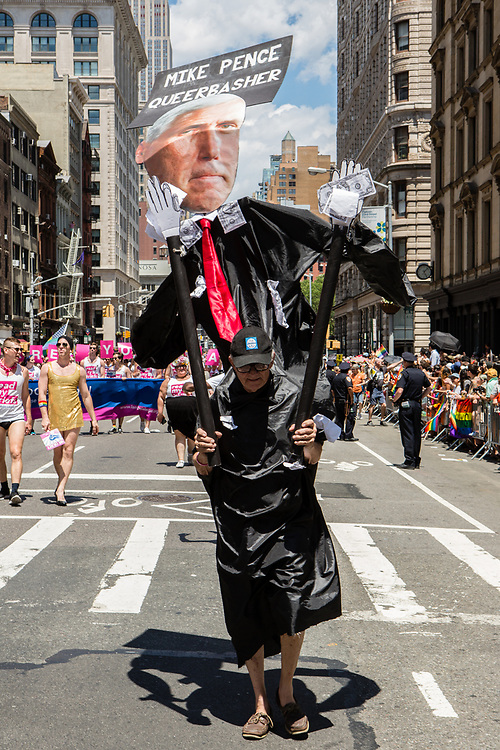 "New York, NY - 25 June 2017. New York City Heritage of Pride March filled Fifth Avenue for hours with groups from the LGBT community and it's supporters. A man with an oversized marionette with the face of Vice President Mike Pence and the caption ""Mike Pence / Queerbasher."""